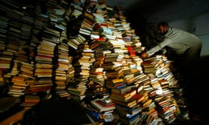 Iraqi assistant Imam Sheikh Mahmood Hachim sifts through the thousands of books in Baghdad's Imam Alhaq Ali mosque in 2003. The books were looted from Iraq National Library after the fall of the capital, with some returned when clerics spoke out.