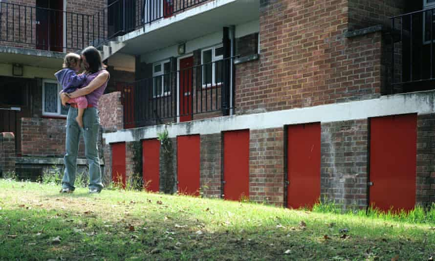 Single woman holds young daughter on council estate