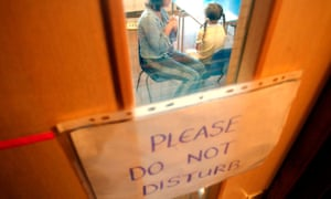 Counsellor talks to a child with Do Not Disturb sign on door