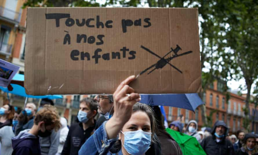 A woman holds a cardboard sign reading: 'Don't touch our children' at a protest in Toulouse last month