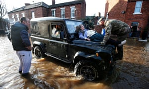 McCraken is helped from her home in Broad Street in Carlisle through the floods by members of the armed forces who have been called in to help evacuate people who wish to move