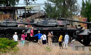 A group of sightseers surround a row of restored tanks in camouflage