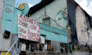 A sign on a building occupied by dozens of homeless families in Rome reads: 'Everything will be fine with income and homes for all'