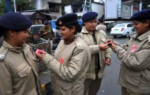 Dehradun, IndiaPolicewomen tie ribbons onto each others uniforms