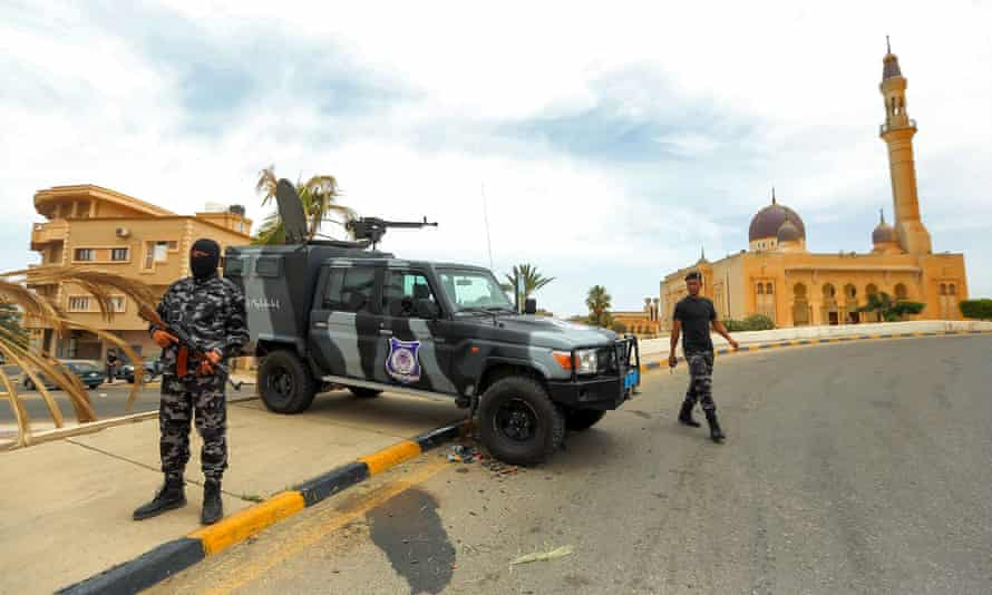 Security forces affiliated with the Libyan Government of National Accord stand at a makeshift checkpoint in Tarhuna