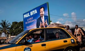 A taxi passes an electoral poster for President Paul Biya