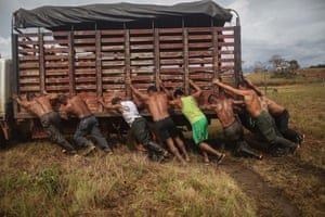 Farc rebels and supporters help push a vehicle following the 10th guerrilla conference in the remote Yari plains