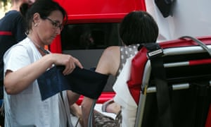 An emergency worker takes the blood pressure of a woman suffering from the heat in Tours, France.