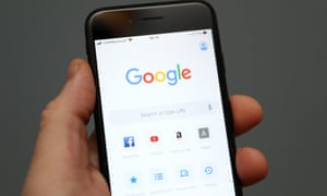 A person is seen holding an iPhone showing the app for Google