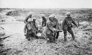 Stretcher bearers struggle in mud up to their knees to carry a wounded man to safety near Boesinghe during the third battle of Ypres.