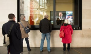 People watch a news report through the windows at BBC Broadcasting House in central London following the death of veteran broadcaster Sir Terry Wogan.