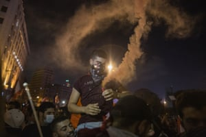 A protester lights a smoke canister as thousands of people descend on central Beirut to protest against the government.