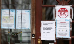 Notices on a GP surgery tell people who think they may be infected to go home and seek NHS advice online.