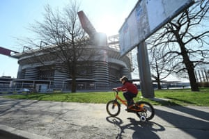 A child rides a bike outside the Milan stadium before the AC Milan v Genoa match is played behind closed doors
