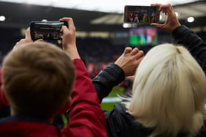 Fans film the players entering on to the pitch.