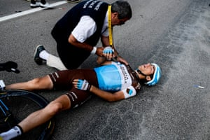 A race medic checks Axel Domont's shoulder after he was caught in a massive pack fall in the close to the finish of the fourth stage between La Baule and Sarzeau.