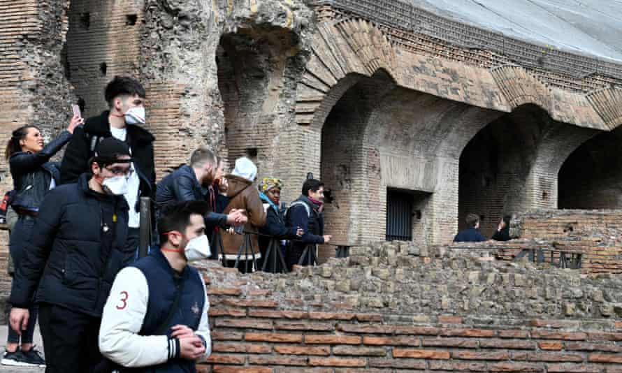 Tourists in Rome wearing respiratory masks visit the Coliseum.
