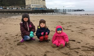 Kaisu Fagan's daughters on the beach at Llandudno, north Wales, where the family are hoping to move to.