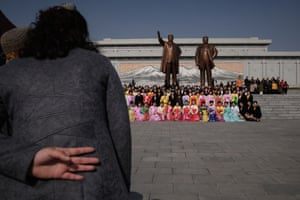 A group of women wearing traditional dress pose for a photo at the statues