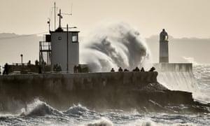 People watch as huge waves hit the sea wall in Porthcawl, South Wales