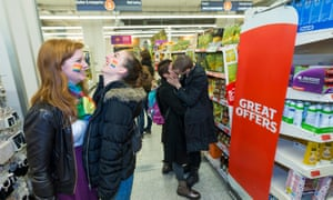 students with rainbow flags painted on their cheeks inside a sainsburys shop