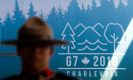 A Canadian mounted police officer stands next to the Charevoix G7 logo