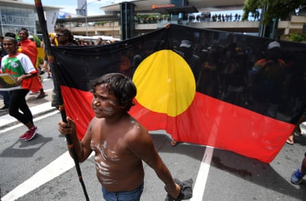 A young Indigenous boy carries a spear at 2017 Invasion Day march in Brisbane.