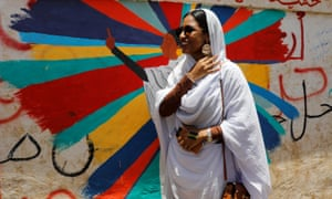 Alaa Salah stands in front of a mural depicting her in front of the defence ministry in Khartoum on 20 April.