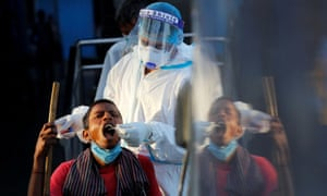 A healthcare worker collects a Covid-19 test swab sample from a man at a temporary shelter for homeless people in New Delhi