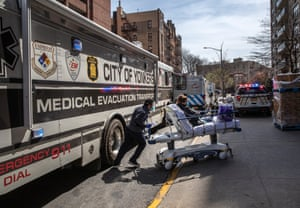 A worker wearing personal protective equipment (PPE), pushes a COVID-19 patient from a specialized bus known as a Medical Evacuation Transport Unit (METU), which carried patients to the Montefiore Medical Center Moses Campus on April 07, 2020 in the Bronx borough of New York City.