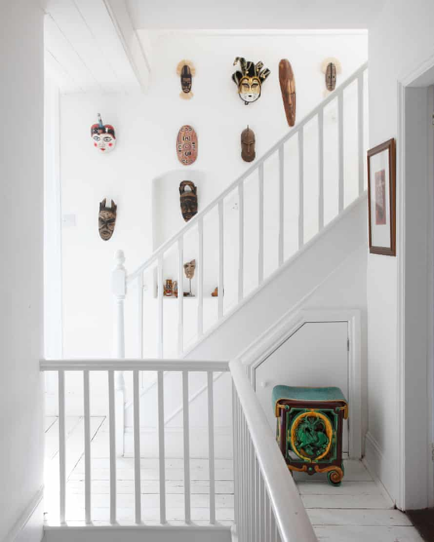 The white stairwell hung with totemic masks.