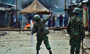 A riot policeman throws a teargas grenade at protesters in Kibera.