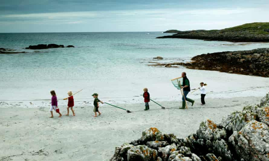 Family walking on a white sand beach on Tiree island in the Inner Hebrides