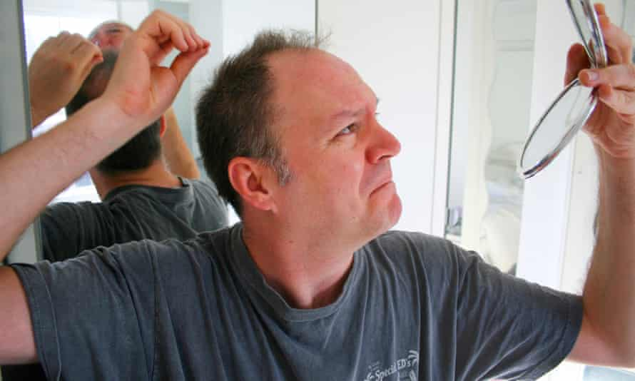 Man looking at back of his head in mirror