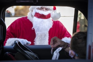 Stan Thompson, dressed as Santa Claus, talks to children in their car during a drive through visit in Indianola, Iowa.