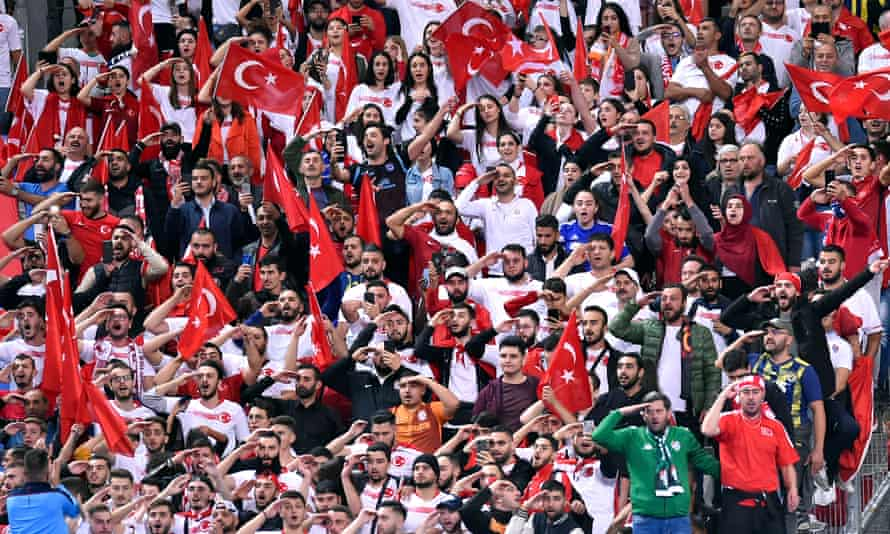 Turkish football fans in Paris respond to the players with their own military salutes.