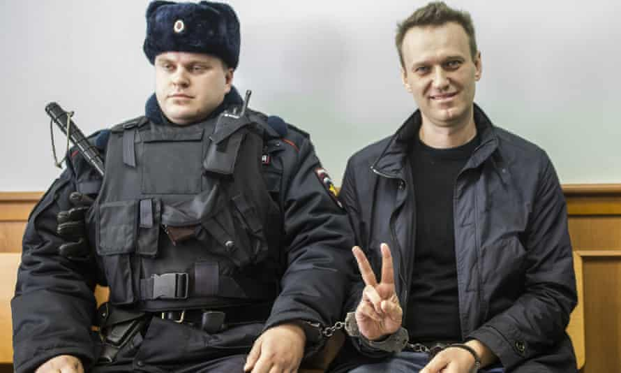 Alexei Navalny shows a V-sign for the media in court in Moscow in 2017.