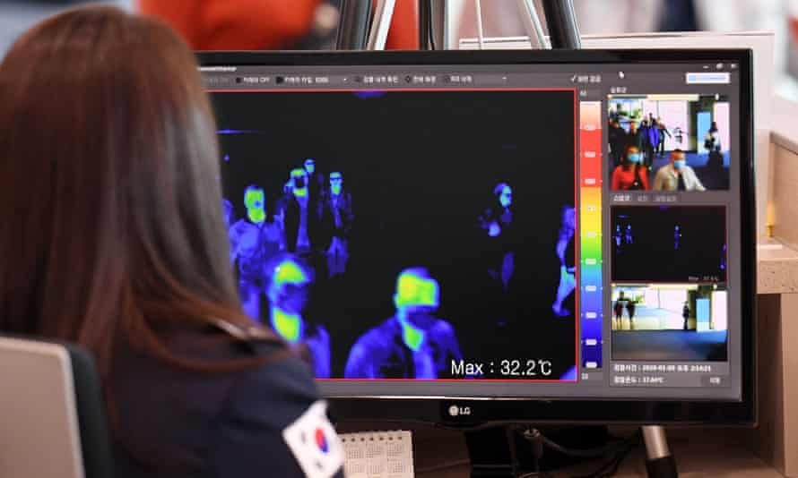 South Korean quarantine officials use thermal cameras to measure the temperatures of passengers arriving from China