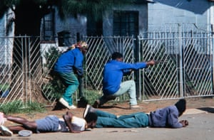 ANC self-defence cadres return fire at Inkatha snipers firing from a nearby mining hostel in the run-up to South Africa's first free elections in Thokoza township near Johannesburg in 1994. During this battle, the photographer Ken Oosterbroek lost his life and several others were badly injured
