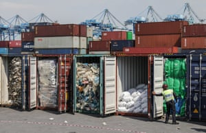 An auxiliary police officer inspects plastic waste in cargo containers in Port Klang, Malaysia
