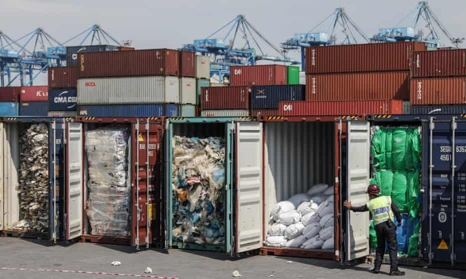 An official inspects waste shipments in Malaysia