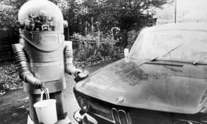 A robot, holding a bucket and sponge, washes a car, circa 1975.