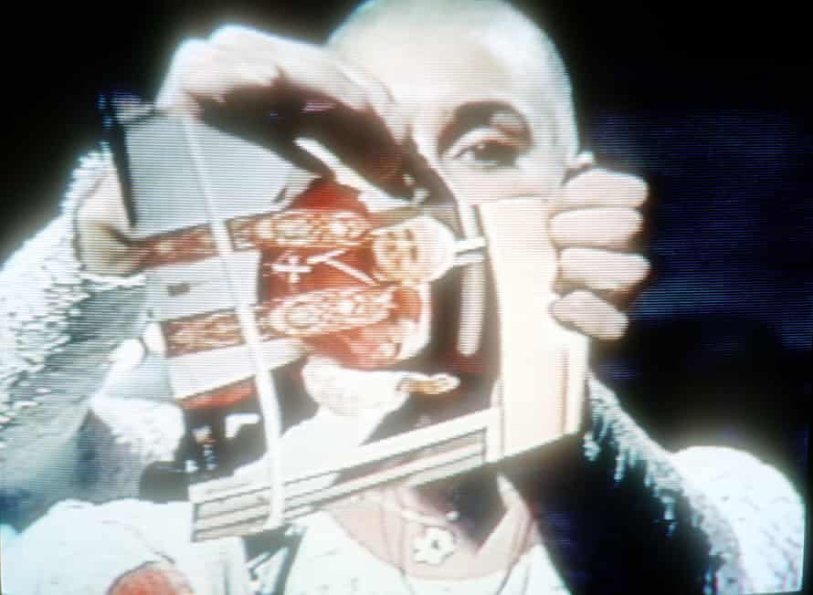 """Sinead O'Connor rips up a picture of Pope John Paul II October 3, 1992 on the TV show """"Saturday Night Live""""."""