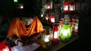A woman completing paperwork by the light of her solar-powered lamps in a village shop for solar products.