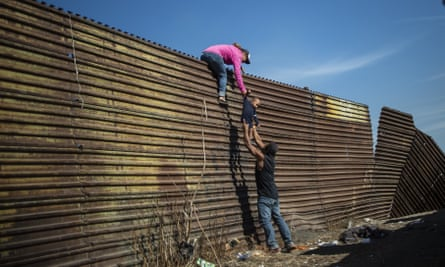A group of migrants climb the fence separating Mexico from the United States.