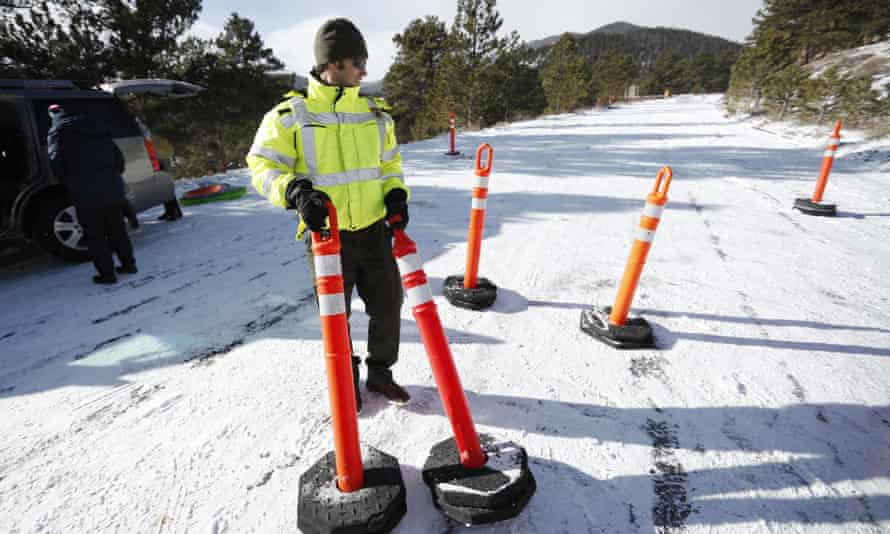 A ranger closes a road in Rocky Mountain national park, where spots remain unplowed.