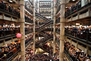 Staff line the atrium as poppies fall during an Armistice commemoration service at Lloyd's of London on 9 November 2018
