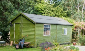 large green garden shed with lawn and wheelbarrow