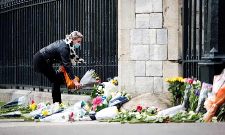 A woman lays flowers outside Windsor Castle