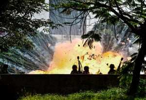 Members of the national guard are caught up in a blast during anti-government protests in Caracas, Venezuela.